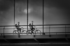 traffic on the bridge (heinzkren) Tags: fahrrad sport bicycle monochrome radfahrer biker biancoetnero blackandwhite schwarzweis couple candid urban bw einfarbig zweirad bridge brücke personen people clouds wolken amsterdam netherlands niederlande cycles fiets geländer railing traffic paar sun sonne street streetphotography panasonic noirretblanc