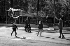 Playing with soap bubbles (l.cutolo) Tags: barcelona blackandwhite bw water monochrome reflections children fun soap spain glow action citylife streetphotography sunlights worldtrekker sharplights softvignette amazingdetails silverefxpro e1855mmf3556oss perfecteffect sharpfocusinthecentre softfocusatthedges bubbledetails