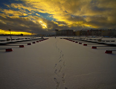 Gone Ice Fishing (MilaMai) Tags: winter sunset sky snow man ice clouds port buildings suomi finland landscape golden dock helsinki sitting tracks footprints human footsteps icefishing frozenocean icefisher milamai vision:text=0501 vision:sunset=0816 vision:sky=0948 vision:clouds=0897