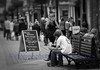 Lunchtime (Photographs by David Hollingworth) Tags: people blackwhite eating couples streetfurniture seating youngcouple shoppers oldercouple streetphotograph menubillboard