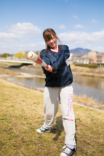 Young woman practicing baseball at riverbank