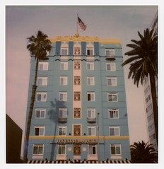 """The Georgian (tobysx70) Tags: the impossible project tip polaroid sx70sonar sonar instant color film for sx70 type cameras impossaroid georgian hotel route 66 ocean avenue santa monica california ca romanesque revival art deco architecture 1933 palm tree us flag stars stripes old glory highrise skyscraper """"the lady"""" rt rte mother road 031017 cromwalk polawalk toby hancock photography"""