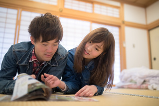 Young couple reading travel magazine in Japanese tatami room