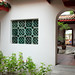Hong San See green-glazed ceramic airbricks in squarish aperture in courtyard wall