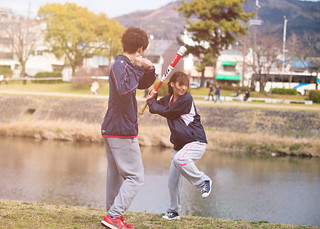 Young athlete couple practicing baseball at bank of Yodo river, Kyoto