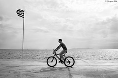 Greece (Georgina ♡) Tags: monochrome blackandwhite portrait candid people shdow bicycle greekflag sea ocean water mountain cloudy manonabike athens greece ripples glistening sailboat bike glasses cment pier