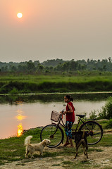 Enjoying the Sunset (Sumit-Gupta) Tags: nepal sunset dogs girl forest river nikon cycle chitwan tamron70300mm narayaniriver d5100