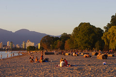 Kits People on the Beach at Dusk (DJ Greer) Tags: ocean trees sunset sea summer people mountain hot tree tower english beach water vancouver bay log sand warm downtown bc towers logs kits kitsilano