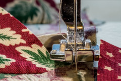 Christmas Quilt in the Making (Marcy Leigh) Tags: hmm macro macromondays inbetween christmasquiltinthemaking quilt sew craft needle foot 14inchfoot thread marcusfabrics millgirlsholiday sewingfoot sewiingmachine fabric christmas holiday hobby lint detail red silver