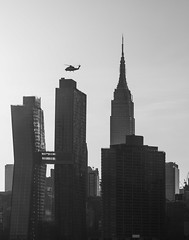 Helitaxi in NYC. (Gimo Nasiff) Tags: gimo nasiff photographer photography helocopter nyc new york city towers buildings esb empire stare building real estate luxury flight flying air transportation urban gentrification gentrified midtown tudor monochrome black whaite sony a6000 ilce6000 ilcea6000 nikkornc85mm18 nikkor nikkorh85mmf18 manual lens dusk travel east west mitakon focal reducer ii zhongyi