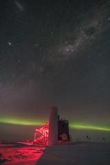 Aurora Horizon (redfurwolf) Tags: southpole antarctica icecube icecubelab snow ice dark night nightsky milkyway stars lmc largemagelaniccloud auroraaustralis aurora outdoor building redfurwolf sonyalpha a99ii sony sal1635f28za lights red green flags