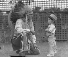 Visiting Indian Chief High Eagle talks with Johnny Schneider (aged about 3 or 4 and dressed in cowboy outfit), White City, Sydney, 11 Jan 1935 / photographer Sam Hood (State Library of New South Wales collection) Tags: boy people photo costume foto menschen mann junge indianer kostm verkleidung begegnung visaliassc
