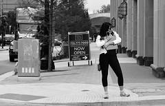 Really Loves Her Bag (burnt dirt) Tags: houston texas downtown city town mainstreet street sidewalk streetphotography fujifilm xt1 bw blackandwhite girl woman people person longhair hug love close standing hugging yogapants tights exercise cellphone phone bag purse waterbottle ramp crosswalk corner