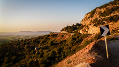 Drive Carefully (Tassos Giannouris) Tags: drive carefully kos greece sunset sign turn road cliff mountains orange landscape sea view trees green