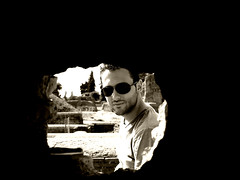 |~You're on the outside looking in~| (jase) Tags: travel light summer portrait people blackandwhite bw italy sun sunlight rome roma guy monochrome smile sunglasses rock person photography grey ruins italia hole forum ruin sunny tint olympus colosseum uomo hombre reminiscence