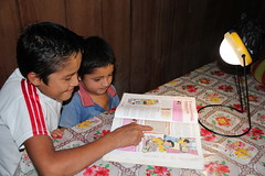"Kids using Sun King Pro to read a book in Villa el Triunfo • <a style=""font-size:0.8em;"" href=""http://www.flickr.com/photos/69507798@N03/13544806543/"" target=""_blank"">View on Flickr</a>"