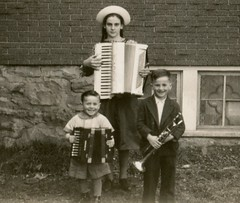 Accordion Kids (Cropped) (Alan Mays) Tags: ephemera photographs photos foundphotos snapshots portraits children boys girls clothes clothing suits dresses hats smiles smiling happy morose unhappy music musicians musicalinstruments accordions accordionists accordionplayers trumpets toys cannons buildings porches bricks windows serrated edges borders antique old vintage