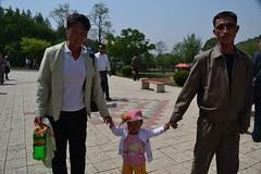 girl with her family (Carpe Feline) Tags: park celebration mayday northkorea pyongyang dprk polaroidcamera carpefeline funfairatthepark
