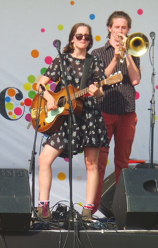 medwayriverfestival band stage australian folk rock beautiful young woman greatlegs guitar performance trombone pose attitude chick chatham sunglasses playing sexy knees hair dark long onstage thighs girl guitarist glasses boots legs unionjack socks kent