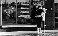 Friendly Staff (burnt dirt) Tags: houston texas downtown city town mainstreet street sidewalk streetphotography fujifilm xt1 bw blackandwhite girl woman people person phone cellphone purse bag man couple pair blonde kiss hug passion tattoo tattooparlor cig cigarette smoke smoking ponytail tights yogapants standing kissing hugging