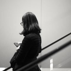 Black hair, out of focus (StephanPhoto) Tags: nyc newyorkcity blackandwhite ny newyork girl manhattan escalator moma smartphone