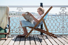 Reading the Sun in the sun (lomokev) Tags: old sea summer portrait sun news female pier newspaper seaside brighton deckchair unitedkingdom samsung brightonpier palacepi