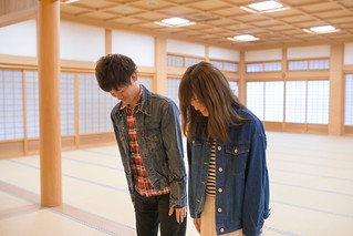 Happy young couple bowing in large tatami room