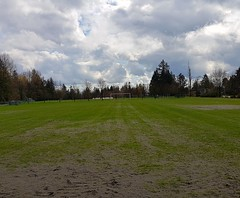 Playing field after the rain (walneylad) Tags: loutetpark northvancouver britishcolumbia canada park parkland urbanpark trees blue sky grey clouds sun sunshine april spring green soccerpitch goalposts scenery view nature playingfield grass mud dirt