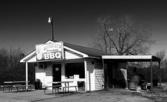 Character's BBQ (Samantha Evans of Samantha Evans Photography) Tags: door trees roof light shadow sky blackandwhite bw sun sunlight black building tree window grass lines sign metal trash canon ga georgia word table awning restaurant words bucket parkinglot closed shadows power country letters bbq tools pole business powerlines shade tables letter americana poles trashcan siding smoker ac asphalt corrugated smalltown picnictable corrugatedmetal adairsville repeatingpatterns repeatingpattern 24105mm adairsvillega canon24105 canon60d charactersbbq