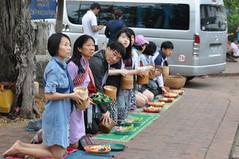 This family has dressed up for the occasion (oldandsolo) Tags: southeastasia earlymorning buddhism tourists lp laos luangprabang buddhistmonk laopdr makingmerit unescoworldheritagecity buddhistreligion takbat buddhistfaith morningalmsgivingritualluangprabang morningalmsgivinginluangprabang