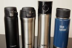 Stainless steel insulated travel mugs on a table (yourbestdigs) Tags: water bottle travel mug coffee thermos hot drink drinks beverage bottles mugs office leak stainless steel insulated warm liquid food lid lids wood desk table dining tea hydration morning breakfast drinking exercising