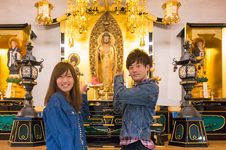 Young couple standing in front of Buddha altar