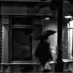 A Rainy Night in St. John's 3 (LongInt57) Tags: person people walking umbrella raining rain wet night sidewalk bw monochrome black white grey gray saintjohns stjohns newfoundland canada lights window noir