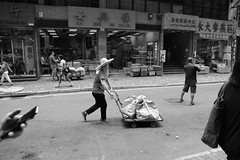Hand Held (Plymography Down Under!) Tags: street city people urban bw hk woman white man black streets men mobile shop female shopping pull mono workers photographer phone market south markets australia hong kong business busy baskets adelaide push bags held cart trolly crowds stalls shoppers jasonnolan plymography wwwplymographycom plymographycom telephonehad