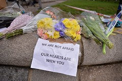 "Floral tributes with a message reading ""We are not afraid, our hearts are with you"", are seen near a police cordon in Westminster in central London on March 23, 2017 a day after a deadly terror attack killed at least three people.  Britain's parliament re"