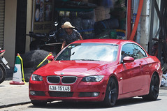 Not her car (Roving I) Tags: women elderly strawhats sunhats street bmw performancevehicles europeancars red danang vietnam vehicles