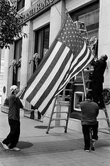 Raising the flag (kuronakko) Tags: sanfrancisco street blackandwhite usa film stairs iso400 flag bank rangefinder patriotic financialdistrict sidewalk ladder atm starsandstripes memorialday wetzlar ilfordhp5plus leitz leicam3 sfbas bwfp leicasummiluxm50mmf14e46preasphlens