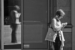Reflecting (Ian Sane) Tags: street camera woman white black reflection window oregon canon portland lens ian photography eos reflecting is downtown phone candid broadway cell images 7d usm sane ef100400mm f4556l