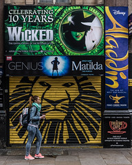 London   |   Musicals Backdrop (JB_1984) Tags: woman person shop store shutter advert poster musical theatre wicked aladdin matilda thelionking street streetphotography theatreland leicestersquare westend cityofwestminster london england uk unitedkingdom
