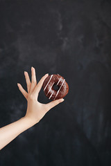 Chocolate donut in a woman's hand on black background (SiberianImages) Tags: background bakery black cafe cake delicious dessert food france french chocolate sweet almond hand handyman home macaroons menu products shop close up closeup assortment bake biscuit blueberry brulee candy coconut coffee color colorful confection cream creme female flavor gourmet green lemon macro orange pastry pistachio put donut brown red tasty