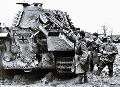 March 13, 1944: Soviet troops celebrate the wrecking of a Panther heavy tank. The tank received a direct hit in the rear, its most vulnerable spot other than the undercarriage. Otherwise, these monsters were immune to all tanks save direct hits from antiaircraft or field cannon