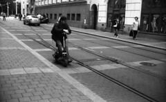 Vilia - Man on a Vehicle (Kojotisko) Tags: street city people bw streets vintage person czech streetphotography brno cc creativecommons vintagecamera czechrepublic streetphoto persons vilia fomapan400 fomapan400action