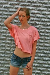 Pink Top Woman (PhotoAmateur1) Tags: pink blue brown brick face wall shirt silver hair necklace arms legs top background stomach lips jeans tummy denim shorts brunette daisydukes