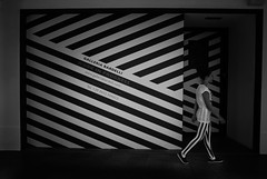 The continuous lines (Giulio Magnifico) Tags: city white black girl lines composition contrast walking funny walk stripes border profile citylife streetphotography catch matching curious udine nikon1v1 1nikkor10mmf28