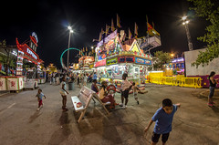 Carnival kids on a Candy high (StGrundy) Tags: carnival blue atlanta red summer usa playing colors yellow kids night contrast dark georgia children lights evening lowlight nikon parkinglot play ride candy nightshot unitedstates south roswell wideangle sugar fisheye southern adobe junkfood cottoncandy rides snacks midway 8mm amusements orientexpress lightroom ringoffire candyfactory ultrawideangle rokinon peachtreerides d7000 stgrundy