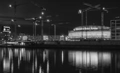 Mercedes Benz Arena plus Kräne (tbird1972) Tags: d800 nikon 50mm 50mm12ais blackwhite blackandwhite silverefexpro2 colorefexpro4 spree berlin river water reflections constructionarea constructioncrane night bynight nightscape cityscape