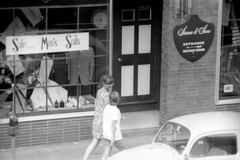 h3-68 13 (ndpa / s. lundeen, archivist) Tags: nick dewolf nickdewolf bw blackwhite photographbynickdewolf film monochrome blackandwhite city summer 1968 1960s 35mm boston massachusetts candid streetphotography citylife streetlife people youngpeople beaconhill charlesstreet sidewalk pedestrians store shop business window windows storewindow simonsons clothingstore street car vehicle automobile parkedcar parkingmeter door doors woman youngwoman pedestrian sign signs women youngwomen sale menssuits tailor tailors cleansers
