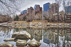 Eau Claire Reflections (John Andersen (JPAndersen images)) Tags: bowriver calgary calm clouds cloudy eauclaire hdr log reflections rocks spring still