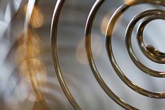Made of Metal (Explored) (1crzqbn) Tags: macromondays spiralwirewhisk refractions macro madeofmetal sunlight bokeh 1crzqbn explore metal