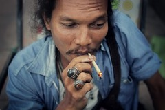 Krung Thep, the city of angels (fredcan) Tags: street travel portrait man face closeup asian thailand southeastasia sitting hand bangkok smoke streetportrait moustache rings krungthep thecityofangels fredcan pagesfredcanongephotography166659476684013